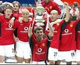 Keane holding aloft the cardboard cup
