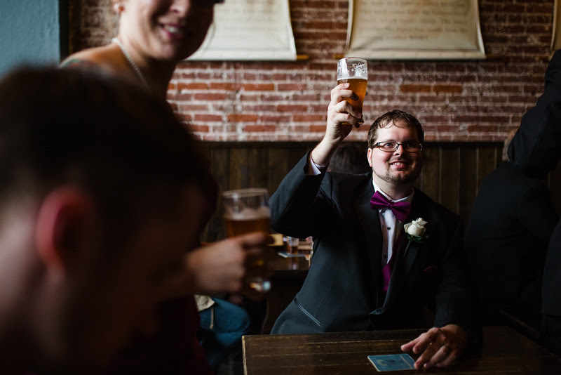 The Best man cheers the bride and Groom following their wedding at Court Street United Methodist Church in downtown Rockford Illinois for an Autumn wedding.
