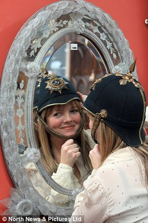 Historic: Jackie Eltringham tries on a Durham Light Infantry helmet - one of the items discovered in the Hermitage