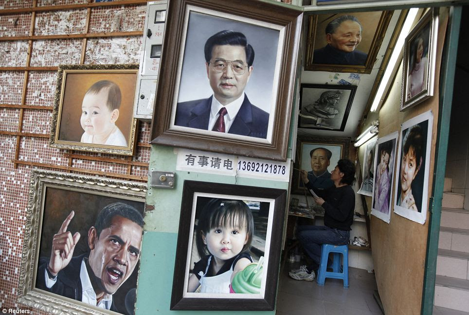 A painter works on an oil painting next to a portrait of China's late Chairman Mao Zedong