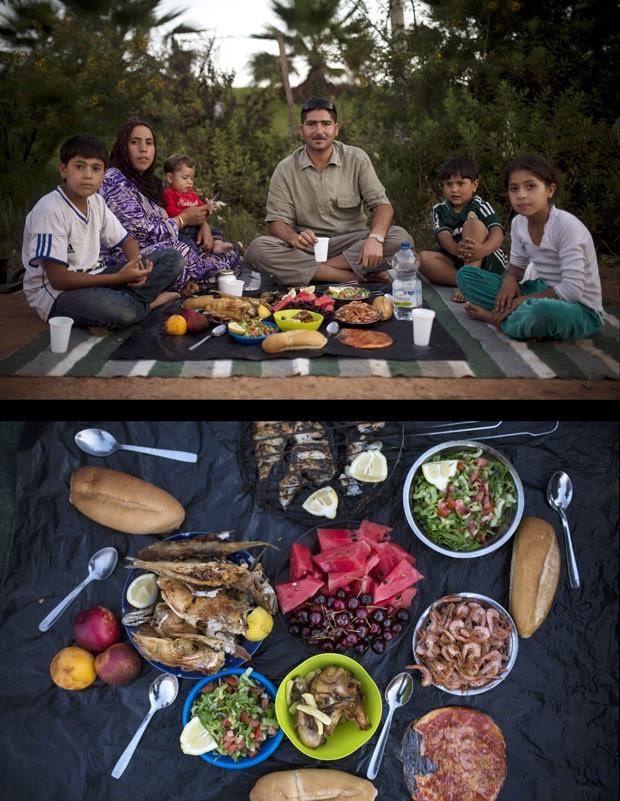 Família de refugiados sírios aguardam o início do Iftar ao lado do Centro para Imigrantes em Melilla, na Espanha. Moradores de Aleppo, eles fugiram da cidade em meio ao conflito armado há 4 meses (Foto: Santi Palacios/AP)