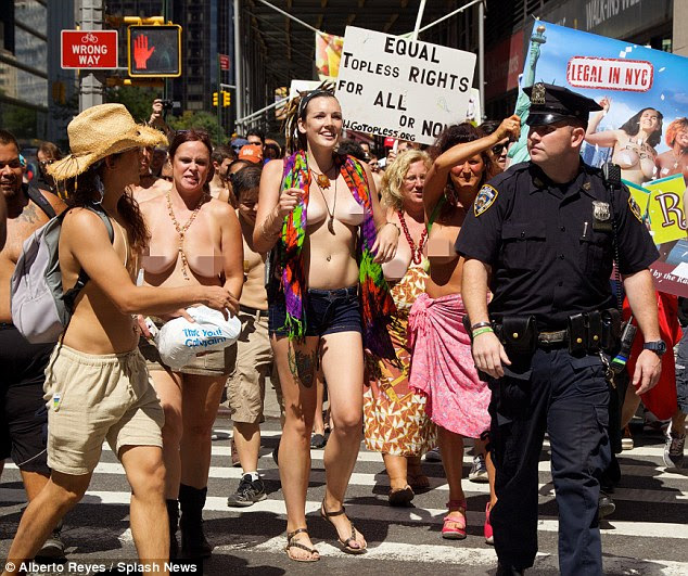 Cops and tops: A stern-looking policeman is flanked by topless women protesting for equal topless rights as men in New York where it is not illegal for women to go topless on the streets