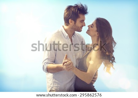 Happy loving couple embracing and kissing outdoors at summertime under blue sky.