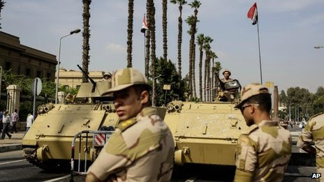 Egyptian military soldiers stand guard near a protest the day before the trial of the former President Mohammed Morsi