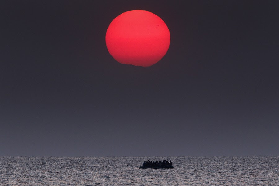 A overcrowded inflatable boat with Syrian refugees drifts in the Aegean sea between Turkey and Greece after its motor broke down off the Greek island of Kos. In 2015 over a million people sought asylum in Europe after departing their war torn and strife addled countries. They crossed in haphazard boats and inflatable dinghies with hundreds perishing at sea (Yannis Behrakis, Thomson Reuters - August 11, 2015).