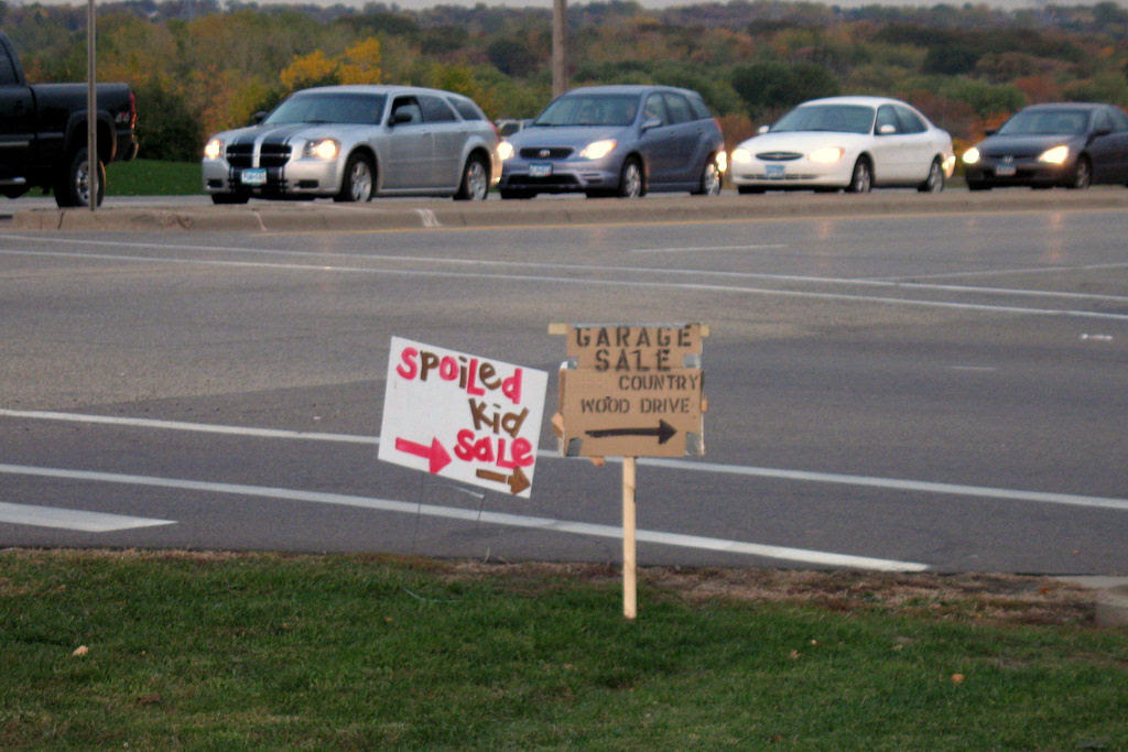 a garage sale sign that reads, spoiled kid sale.