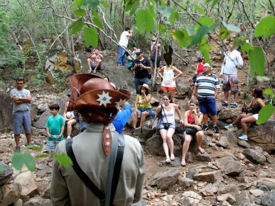 Na Grota de Angico, grupo ouve explicação de guia sobre as emboscadas feitas contra o bando de Lampião (Foto: Waldson Costa/G1)