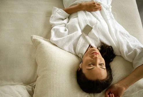 Mulher usando fones de ouvido, enquanto relaxa na cama