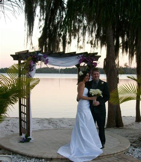 Bride and groom at the arbor arch in front of the beach