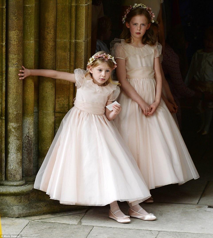 Duas das damas de honra mais jovens, vestindo belas de estilo vintage tule vestidos cor de rosa pálido, magro contra um pilar de pedra no histórico Romsey Abbey