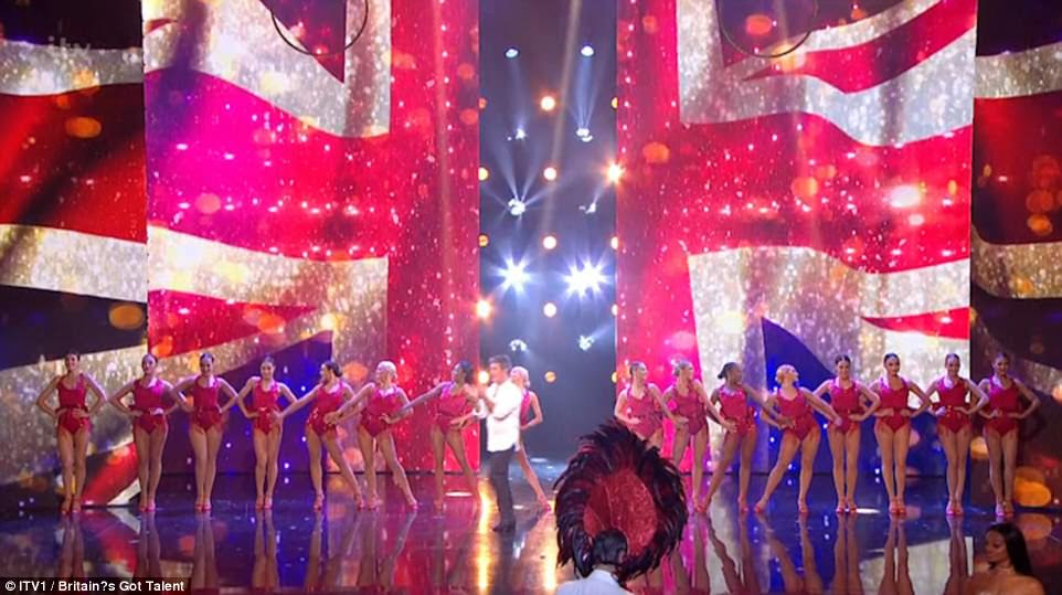 A chorus line: Simon worked the stage as a number of red leotard-clad dancers stood behind him