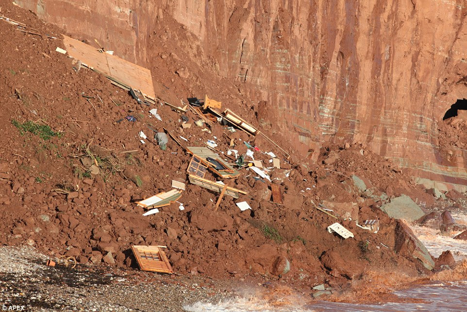 Look out: Today broken pieces of wood, along with sections of window and garden furniture can be seen scattered on the rocks next to Sidmouth's East Beach