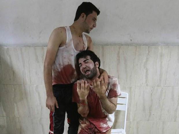 Homem com roupas manchadas pelo sangue é consolado em hospital em Khan Younis: cerca de 1.900 palestinos morreram em Gaza (Foto: Reuters)