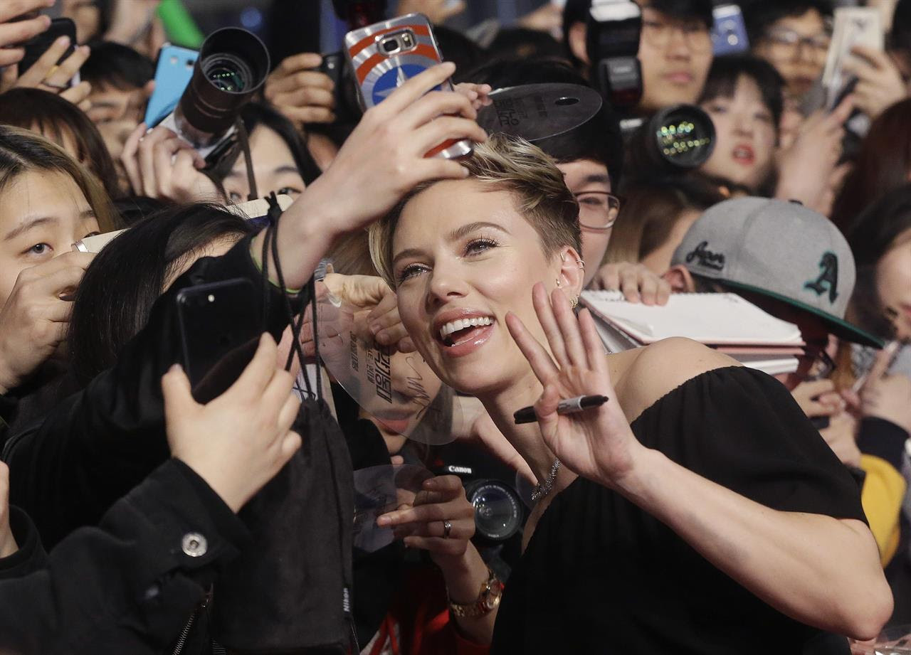 "In this Friday, March 17, 2017 photo, actress Scarlett Johansson poses with fans for a selfie during a promotional event for her latest film ""Ghost in the Shell"" in Seoul, South Korea. The film will be released in South Korea on March 29."
