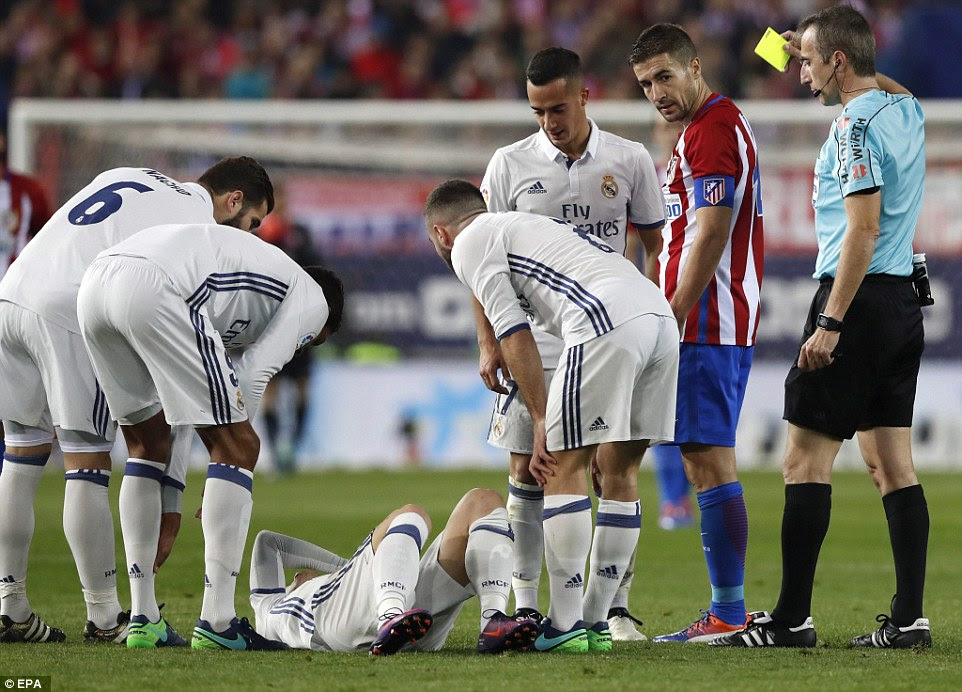 Atletico Madrid midfielder Gabi is shown a yellow card as the Real Madrid players crowd around the stricken Luka Modric