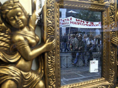 Un grupo de periodistas griegos, reflejado en un espejo de una tienda de antigüedades, protesta en contra de las nuevas medidas de austeridad.  EFE/Orestis Panagiotou
