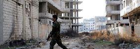 Un soldato del regime passa attraverso un danneggiata dai bombardamenti nel sud della Siria Straßenzug Daraja.