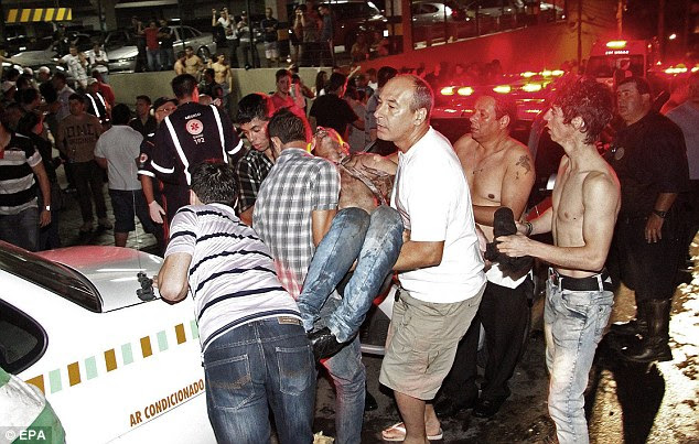 Carnage: Locals help evacuate injured victims as clubbers look on in horror following the nightclub fire