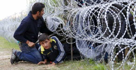 Refugiados sirios cruzan debajo de una alambrada con cuchillas e la frontera entre Hungría y Serbia, cerca Röszke.- REUTERS / Laszlo Balogh