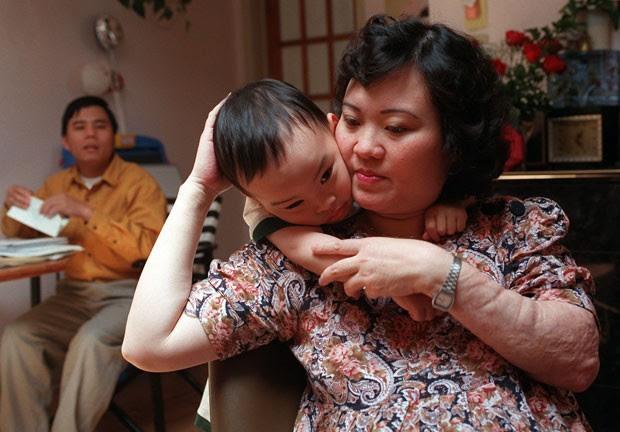 Em imagem de 1997, Kim Phuc aparece com o filho e o marido no apartamento da família em Toronto (Foto: Nick Ut/AP)