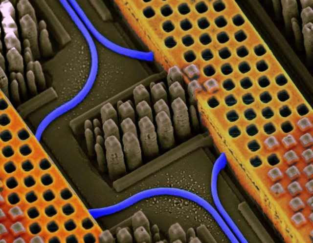Angled view of a portion of an IBM chip showing blue optical waveguides transmitting high-speed optical signals and yellow copper wires carrying high-speed electrical signals