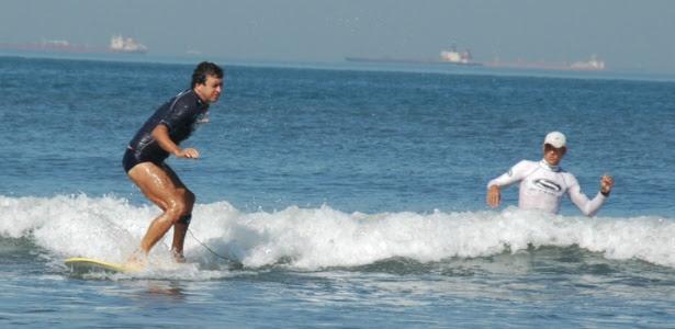 Valdemir Pereira Corrêa surfa com auxílio de seu professor Cisco Araña na Escola Radical, em Santos (SP)