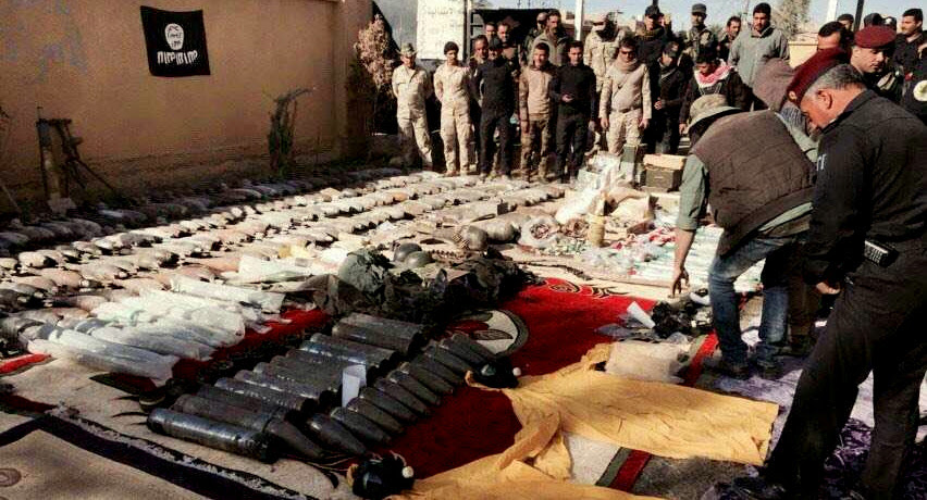 Iraqi security forces look at confiscated ISIS weapons and ammunition after regaining control over the last week, in Ramadi, Iraq's Anbar province, 70 miles (115 kilometers) west of Baghdad, Thursday, Dec. 10, 2015.