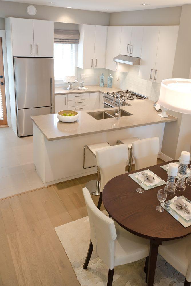 Una barra entre la cocina y el comedor hace que la cocina se vea un poco más pequeña pero ayuda a delimitar las dos áreas sin necesidad de paredes.