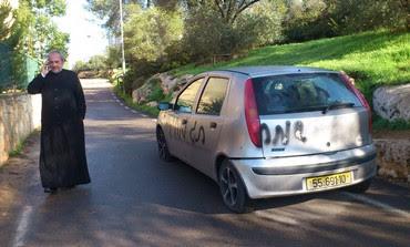Father Claudio near spray-painted car