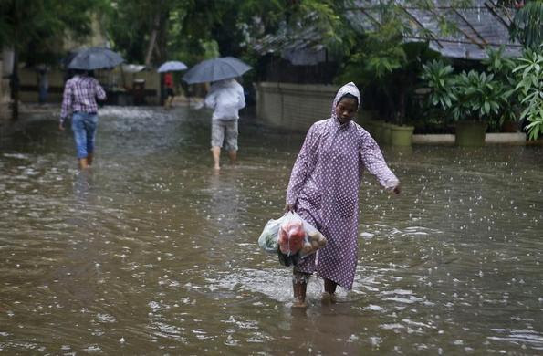 A woman carries vegetables as she walks though a flooded street during monsoon rains in Mumbai, June 16, 2013.  REUTERS-Danish Siddiqui