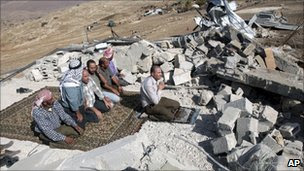 A group of Palestinian men pray on the ruins of a mosque in Khirbet Yarza