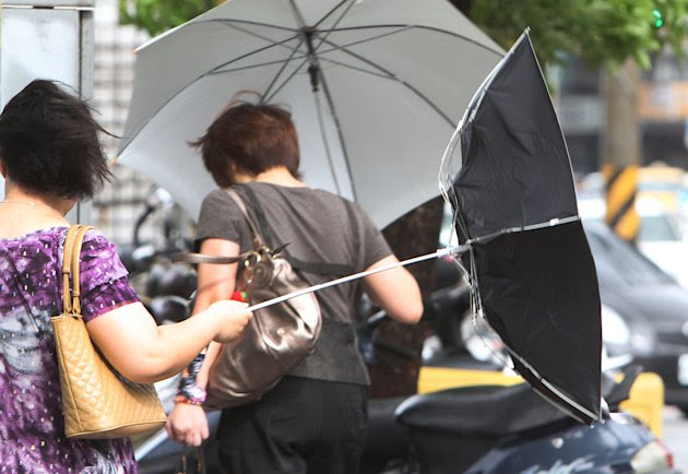 A woman with an umbrella is caught by powerful gusts of wind generated by typhoon Nanmadol in Taipei, Taiwan, Monday, Aug. 29, 2011. Typhoon Nanmadol has slammed into Taiwan, closing schools, workplac