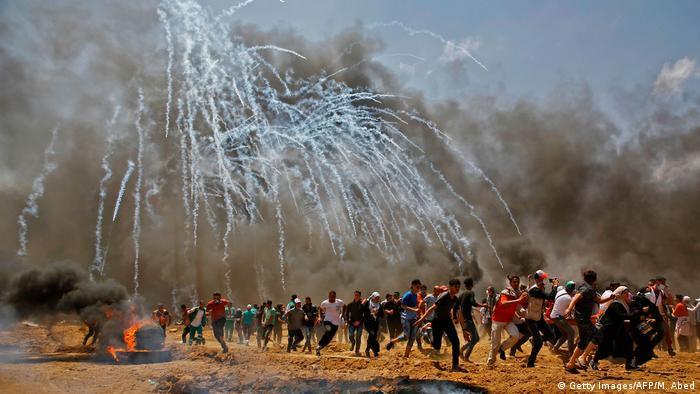 Palestinos em meio a gás lacrimogêneo na região fronteiriça entre a Faixa de Gaza e Israel