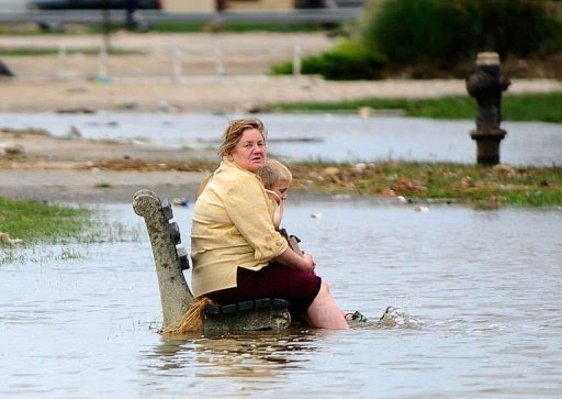 A woman and a child sit on a public bench amid floodwater