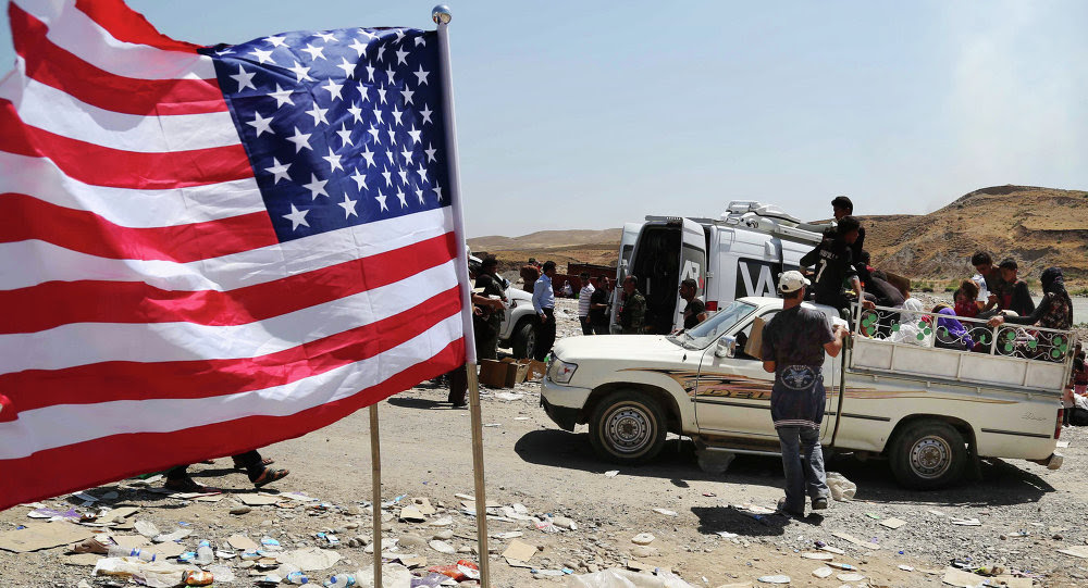 US flag waves while displaced Iraqis from the Yazidi community cross the Syria-Iraq border on Feeshkhabour bridge over Tigris River at Feeshkhabour border point, northern Iraq