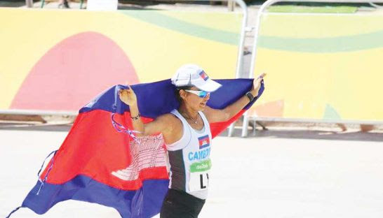 Nary Ly drapes the Cambodian flag around her after crossing the finishing line of the 2016 Rio Olympics women's marathon on Sunday. Photo supplied by NOCC
