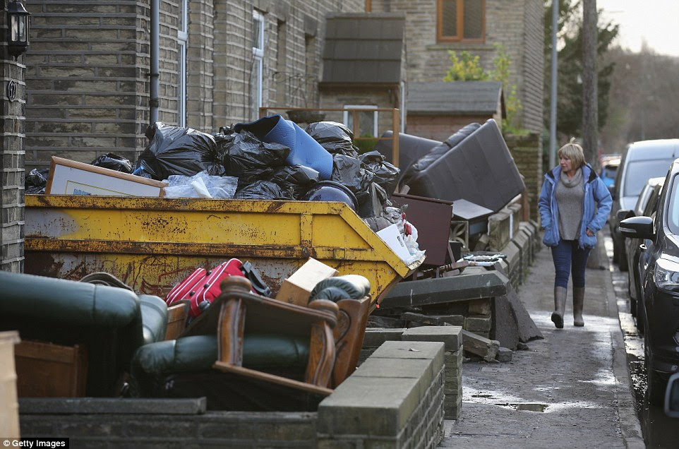 Surveying the scene: Residents clean up the damage caused by flood waters in the village of Elland in West Yorkshire today