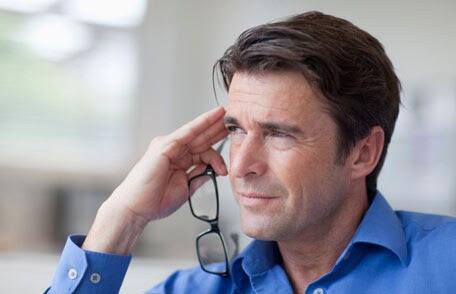 Middle-aged man holding eyeglasses