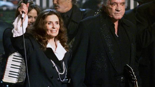 DEVOTED COUPLE: Johnny Cash and his wife June wave to fans at the end of a tribute in his honour in 1999.