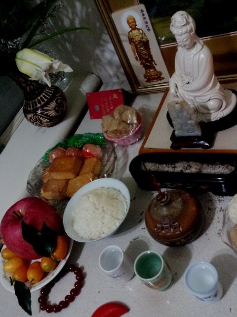 Taipei・Chinese New Year's Eve:New Year's dishes, and pray on god for to get rich, to make a fortune and to make a pile… (photo: Feb. 9, 2013)台北・除夕:農暦大晦日 御節をいただく建物の最上階に私の大家(房東)がお住みである。電話を受け、正月用にと御節を受け取りに上がる。信心深い、というか現世実利を尊ぶ大家、健康に、家族円満に、そしてもっとも重きを置いている発財・金儲けを神頼みにして、写真のごとく仏像を飾り、香を炊き、花を手向け、お供物を捧げ、お経を流し、般若心経を念じておられる。ではでは 新年快楽 恭喜發財 紅包拿來 よき年を迎えられるよう、私も拝拝いたしました。