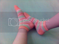 feet in colorful socks, against the wall 2005