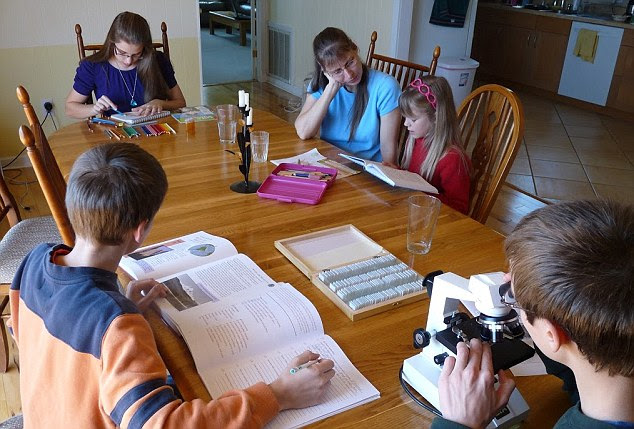 The school day in the Romeike household is a conducted around the kitchen table, with Uwe making the rounds as her children study