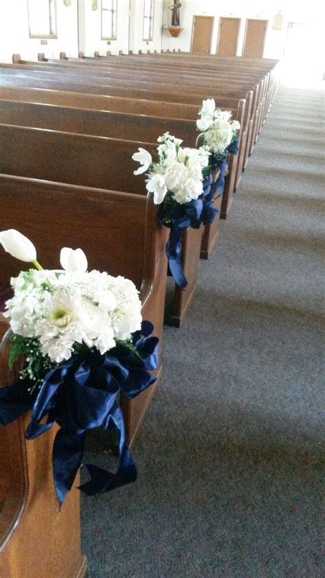 pew decor white flowers with navy blue ribbon.   Sacred