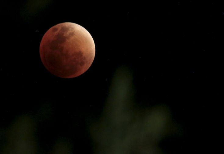 The Moon, appearing in a dim red colour, is covered by the Earth's shadow during a total lunar eclipse ove La Paz