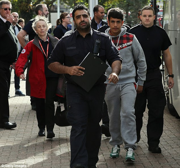 Aimal Khan, 14, dressed in a grey 'hoodie' and jogging bottoms is escorted to the Home Office branch in Croydon, south London, after arriving from the Calais Jungle camp. Some 14 youngsters are believed to have made the journey today