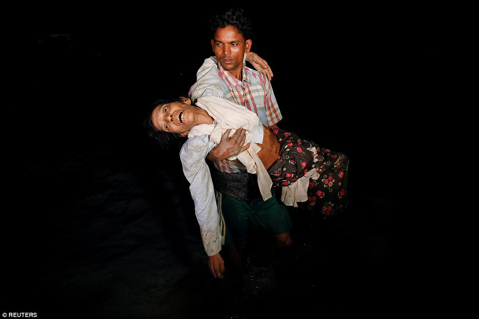 Rohingya refugee Nobi Hossain wades through water carrying his elderly relative Sona Banu, as hundreds of others fled Myanmar in wooden boats under the cover of darkness to arrive at the shore of Shah Porir Dwip, in Teknaf, Bangladesh, on September 27