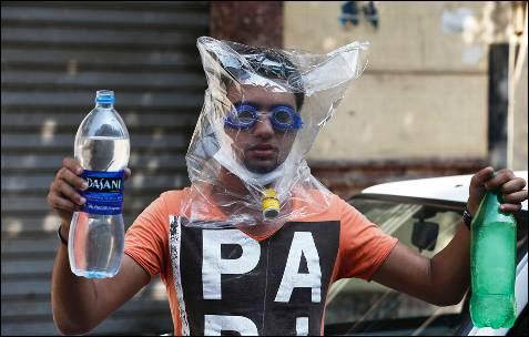 Un partidario del depuesto presidente egipcio, Mohamed Mursi cubre su rostro con un plástico para evitar el gas lacrimógeno durante una protesta frente a la Mezquita Al-Fath en la plaza de Ramsés.