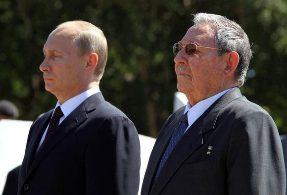Russian President Vladimir Putin (L) stands next to Cuba's President Raul Castro as they attend a wreath-laying ceremony at the Soviet Soldier monument in Havana July 11, 2014.  REUTERS/Alejandro Ernesto/Pool