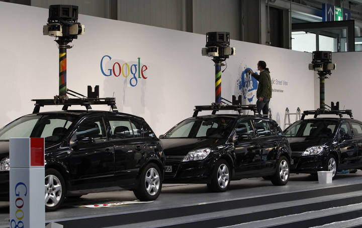 """A worker makes final touches at the stand of Google where cars used for """"Google View"""" are on display at the CeBIT exhibition centre in Hanover"""