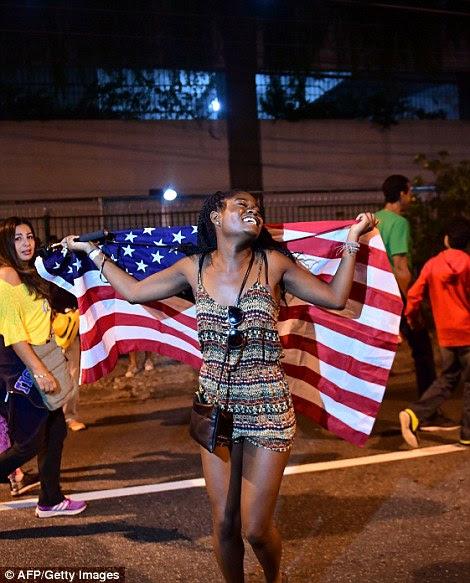 Um ventilador detém a bandeira dos Estados Unidos fora do estádio do Maracanã, no Rio de Janeiro